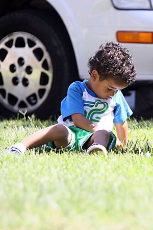 A little boy sitting on the grass picking at it, looking sad.