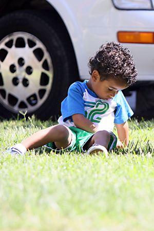 Een jongetje zittend op het gras picking op het, op zoek triest. Stockfoto