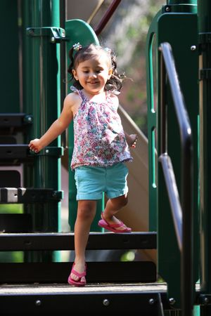stepping: Little girl stepping down from the playground equipment