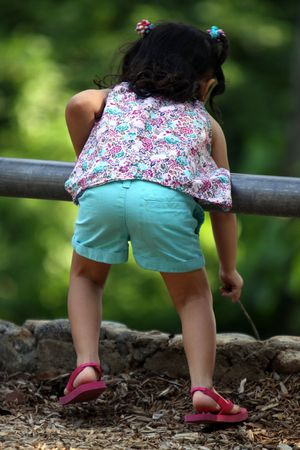 Little girl leaning over a railing with a stick in her hand, pretending to fish Imagens