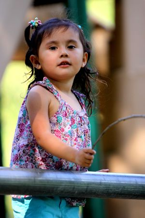 Cute Little girl with a stick at a playground photo