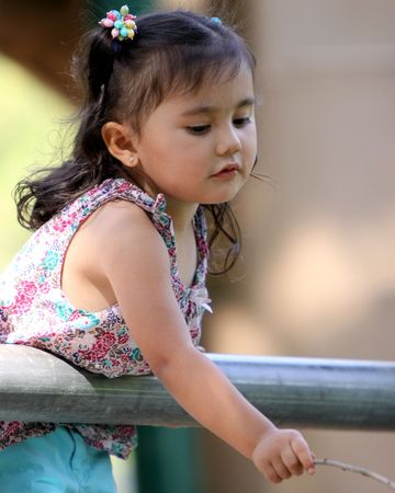 Little girl leaning over a railing