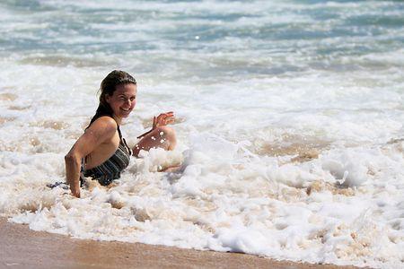 若い笑顔の女性、水の端で右に座って海を楽しんでします。 写真素材