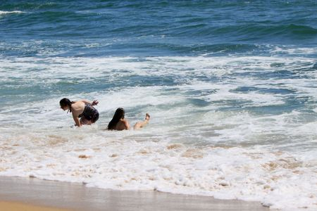 knocked over: Two young women, just knocked over by a wave.