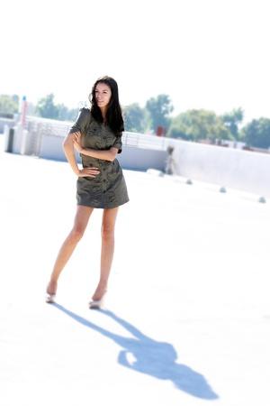 立体駐車場で明るい日にショート ドレスとハイヒールを着て女の子。