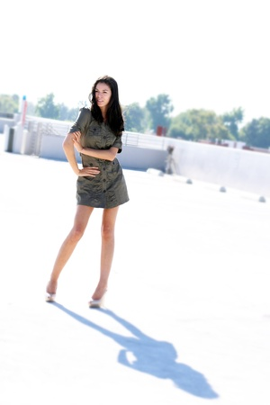 A girl in a parking structure, wearing a short dress and high heels, on a bright day.