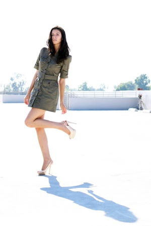 A tall young girl in a short dress and high heels, outside with the bright sun casting a shadow of her on the ground.