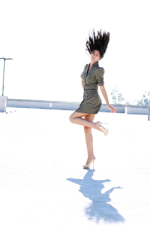 A tall girl in a short dress and high heels with her hair flying up in the air. Фото со стока