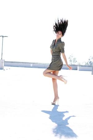vestido corto: Una chica de altura en un vestido corto y tacones altos con su cabello volando por el aire.