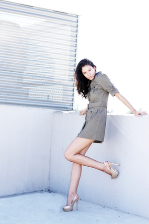 A sexy brunette, standing outdoors in a concrete parking structure, wearing a short dress and high heels.