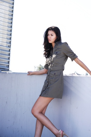 A pretty, tall and thin brunette, standing outdoor, leaning against a concrete wall