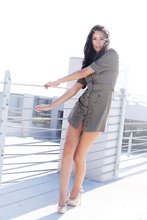 A long legged brunette standing in a parking structure, holding onto a wire fence.