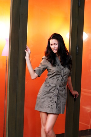 若い女性モデルは、オレンジ色の彼女の後ろにライトとガラス窓の前に立っています。