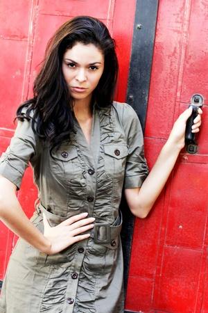 赤い鋼鉄ドアのそばに立ってかなりブルネットの少女。