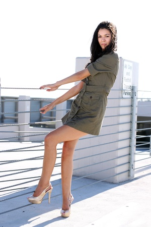 A young woman in a short dress, holding onto a wire fence in a parking structure, looking as though she may be thinking about climbing over it.