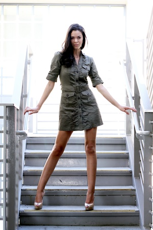 背の高い、薄い、彼女の後ろに明るい日光の下でいくつかの階段に立っている女の子。 写真素材