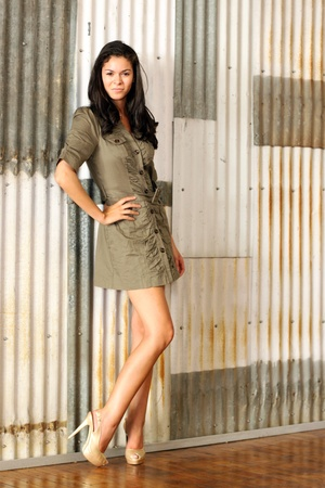 tall and short: A pretty brunette woman in a short dress and high heels, indoor, standing in front of a corrugated wall.