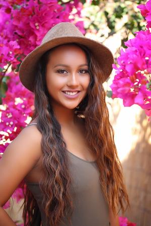 美少女のピンク色の花の庭の帽子をかぶって