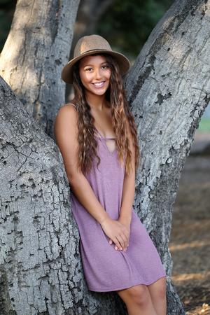 木のクルックに座っているかわいい女の子