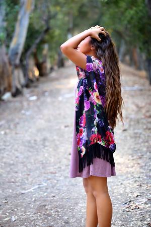 未舗装の道路上のプロファイルで立っている女の子
