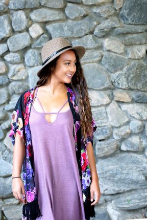 Happy, smiling girl near a rock wall