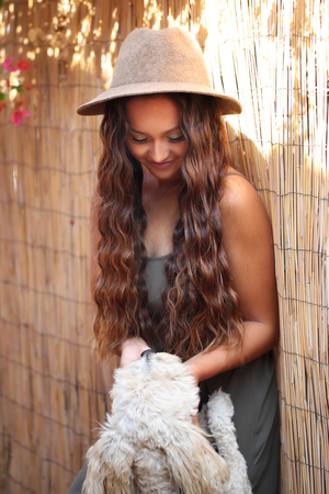 Girl in hat petting a dog