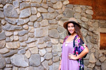 Pretty girl near a rock wall Фото со стока