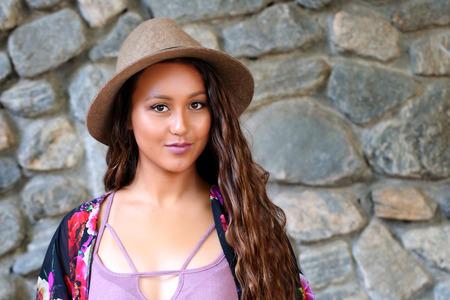 石造りの壁の近くの帽子でかわいい女の子