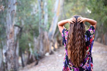 Long haired girl among trees