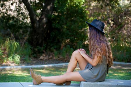 Girl sitting and thinking Фото со стока