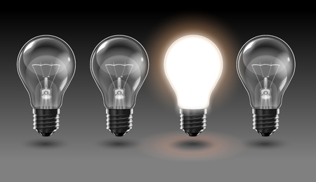 Four transparent light bulbs, one of which is brightly lit, on a dark gray background.