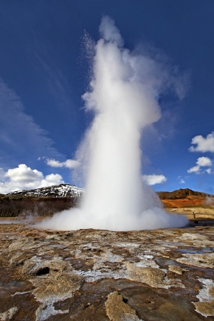 Icelandic Geyser erupts, with blue sky in the background Stock Photo