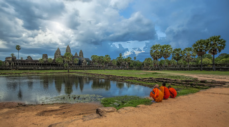 angkor wat: Monks watching the sunset over Angkor Wat from the lake
