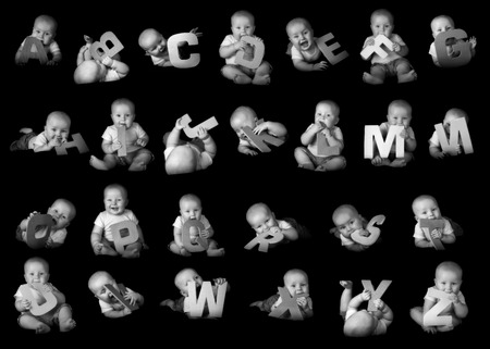 Baby boy holding alphabet letters isolated on black