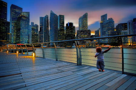 sunset city: Little boy in a big city at sunset