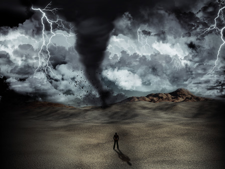desert storm: Silhouette of a man stood in the desert in the middle of a storm with tornado and lightning