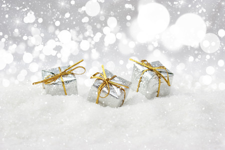 nestled: Silver Christmas gifts nestled in snow Stock Photo