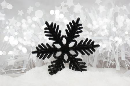 nestled: Christmas snowflake decoration nestled in snow