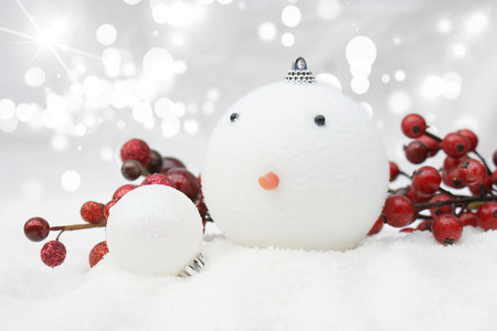nestled: Christmas snowman bauble nestled in snow Stock Photo