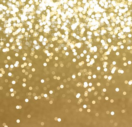 Glanzend goud Kerst achtergrond met sterren en bokeh lichten Stockfoto