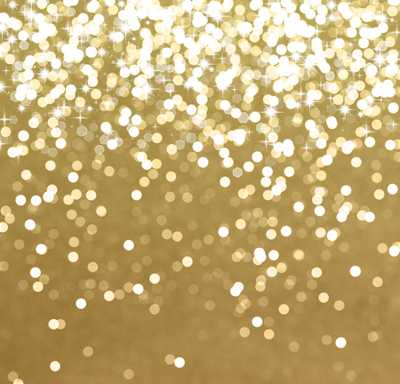 Glittery gold Christmas background with stars and bokeh lights