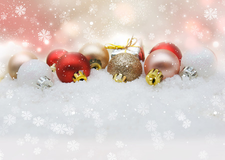 nestled: Christmas decorations nestled in snow Stock Photo