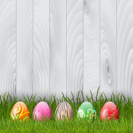 egg: Decorative Easter eggs in grass on a wood background