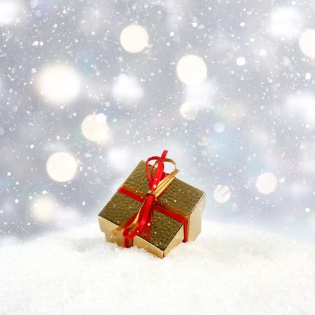 Gold Christmas gift nestled in snow Stock Photo