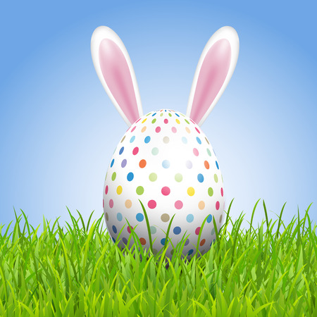 Easter background with bunny ears and egg nestled in grass