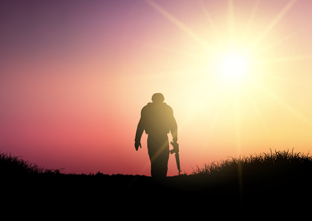 Silhouette of a soldier walking against a sunset sky