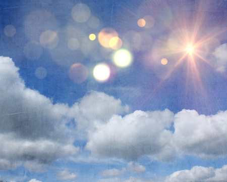 Grunge style background with sunshine and clouds on blue sky