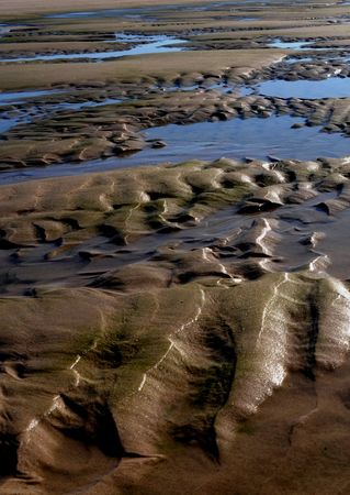 Sand on a beach shaped by waves