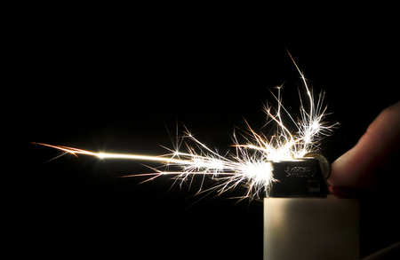Sparks take colorful crystalline shapes as they come out of a cigarette lighter. Stock Photo
