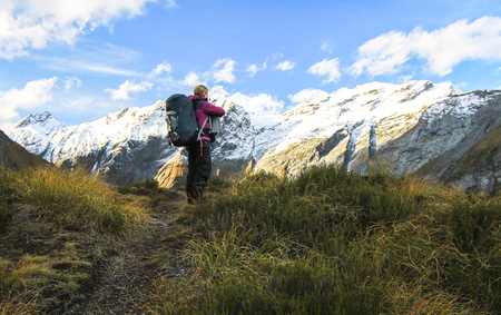 A hiker stops to admire a stunning view in the Mt. Aspiring National Park on New Zealands south island.